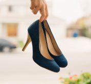 Femme qui tient des chaussures à talons à la main